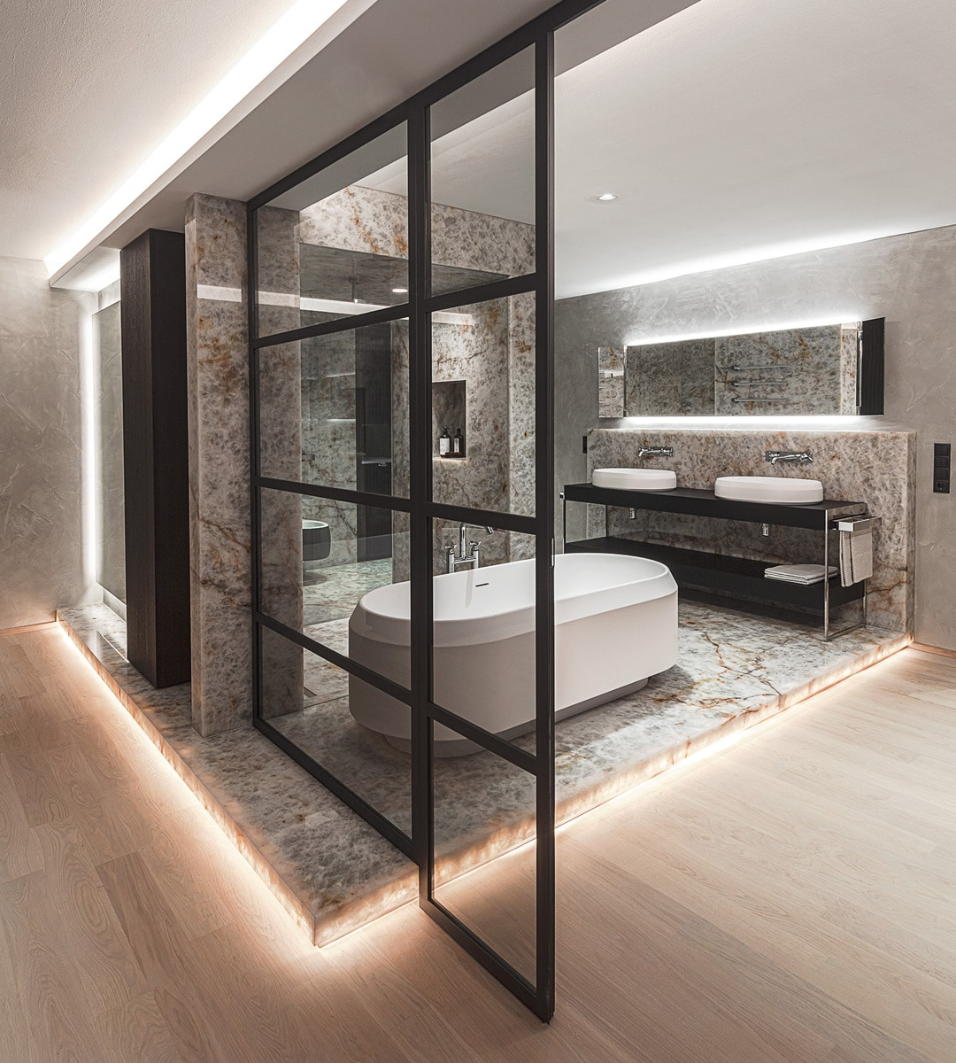 Badezimmer O.: In der Wiener Stadtwohnung wurde von M&G ein Badezimmer der Extraklasse geschaffen. Die offene, wohnliche Gestaltung mit Glastüren und Holzböden wird mit dem Podest und den Wandelementen aus White Iceberg (Kristallmarmor) von Breitwieser förmlich gekrönt.