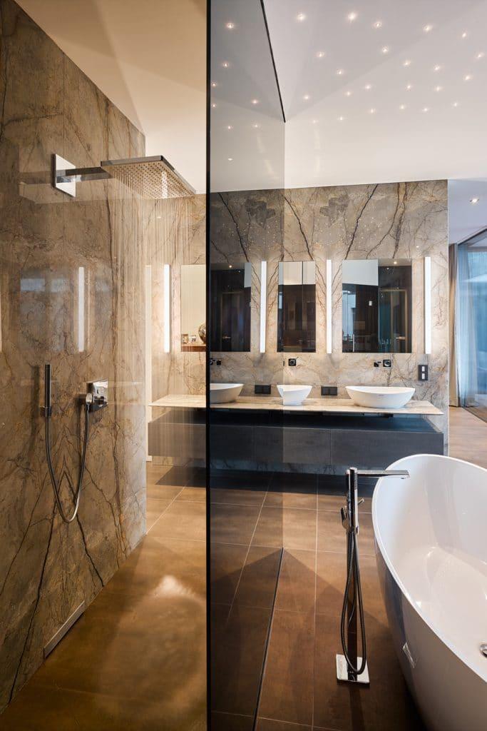 Große Wände aus Silver-Roots-Marmor von Breitwieser verkleiden das extravagante Badezimmer.