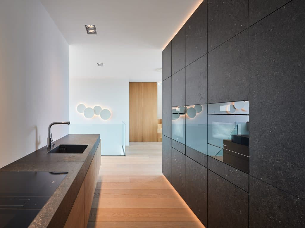 Die Wohnküche im Penthouse H. wurde in schwarzem Kalkstein (Pierre Bleu Pec) mit grober Oberfläche ausgeführt. Die rohe Haptik des handgeschliffenen Steins setzt auf Natürlichkeit auf der Fläche und an der Wand.