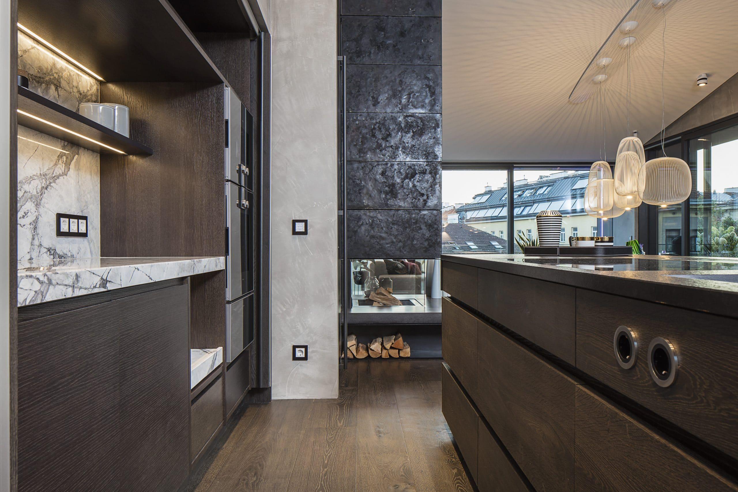 """Die Showloft-Küche im FORMDEPOT, 1160 Wien, setzt auf starke Präsenz, aber Wandlungsfähigkeit. Als Theke, Barelement oder vollwertige Küche ist sie optisch und funktional immer im Zentrum. Wichtiger Akzent: die elegante und """"gewichtige"""" Steinhaube aus schwarzem Basalt (Nero Assoluto)."""