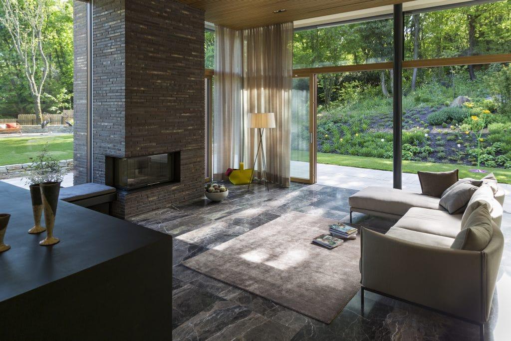 Die Villa am Waldrand von Atelier Claus Radler setzt auf zeitlose und dauerhafte Materialien. Neben dem Pool, den Steinmauern, den Terrassen und der Wegeführung in der sehr natürlich gewachsenen Gartengestaltung von Clemens Lutz kommt im Wohnzimmer ein schöner türkischer Marmor von Breitwieser zum Einsatz