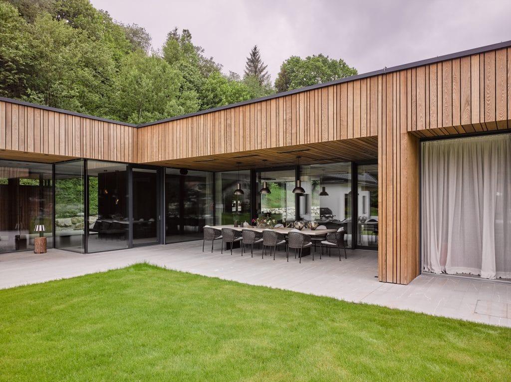 Ein moderner Zubau ergänzt nun das alte Landhaus in Niederösterreich. Ob man sich im alten oder neuen, ob man sich drinnen oder draußen aufhält – es ist nicht immer gleich ersichtlich. Die Grenzen verschwimmen. Der großflächige Einsatz von Stein trägt zu diesem Effekt besonders bei.