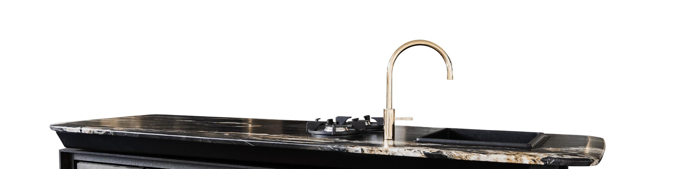 """Die Küche """"Turntable"""" kann In- und Outdoor und vereint optische Lockerheit mit kompakter Funktionalität. Arbeitsplatte und Fronten bestehen aus frostsicherem """"Golden Viper""""-Granit. Die Raffinesse: Der Unterbau wird zum """"Turntable"""" und damit eine erweiterte Arbeitsfläche."""