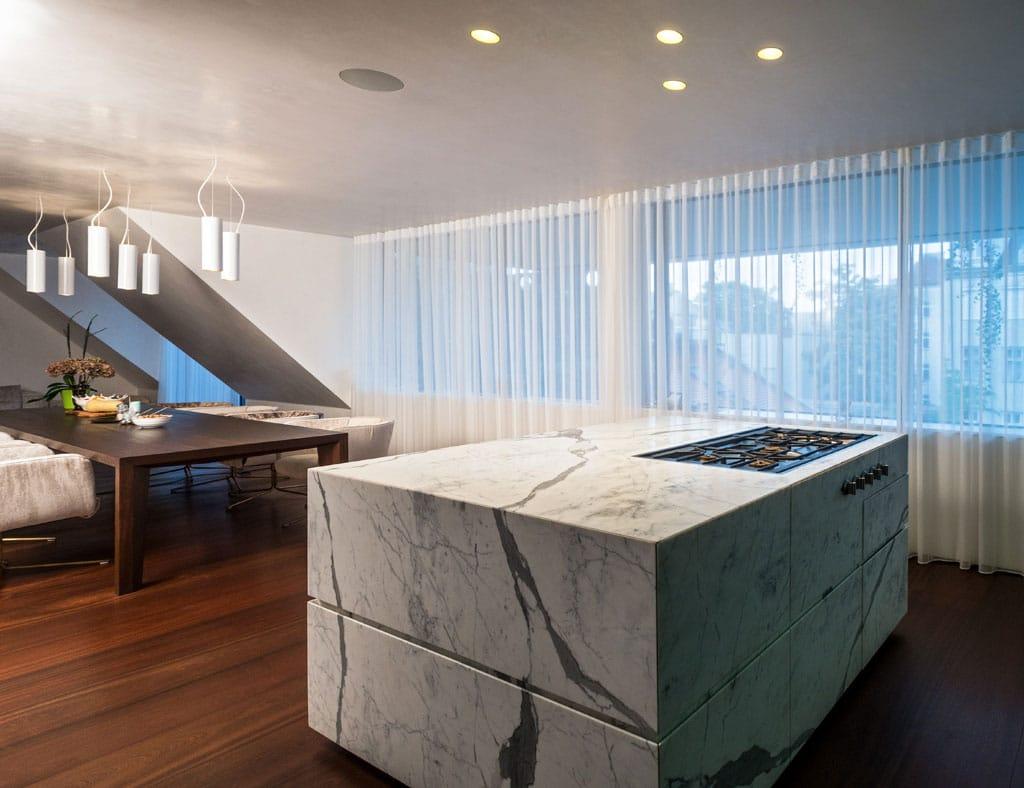 Der Küchenblock und die Arbeitsplatte in der Wohnung H. wurden kontrastreich in weiß-grau gemustertem Marmor und dunklem Holz ausgeführt.