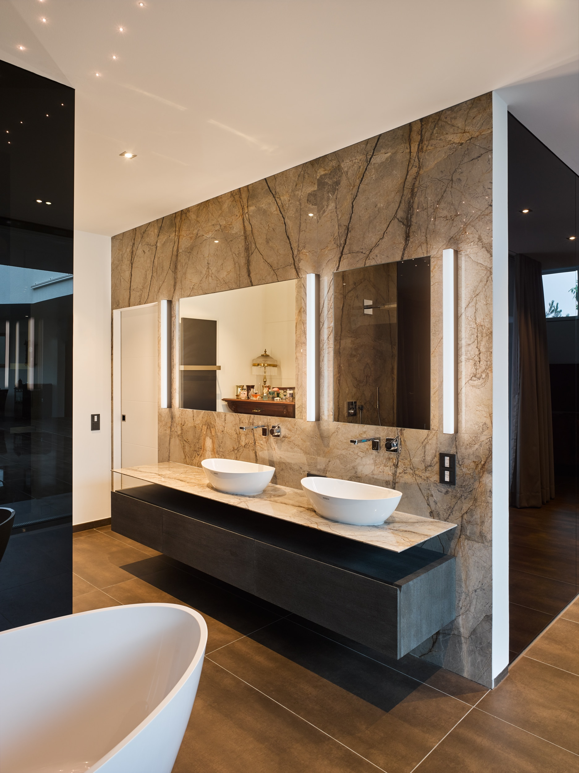 Große Wände aus Silver-Roots-Marmor verkleiden das extravagante Badezimmer. Ein spektakuläres Muster, wie silberne Wurzeln auf einem Waldboden. Die Architektur, klar und schlicht, gibt dem Marmor Raum und Bühne.