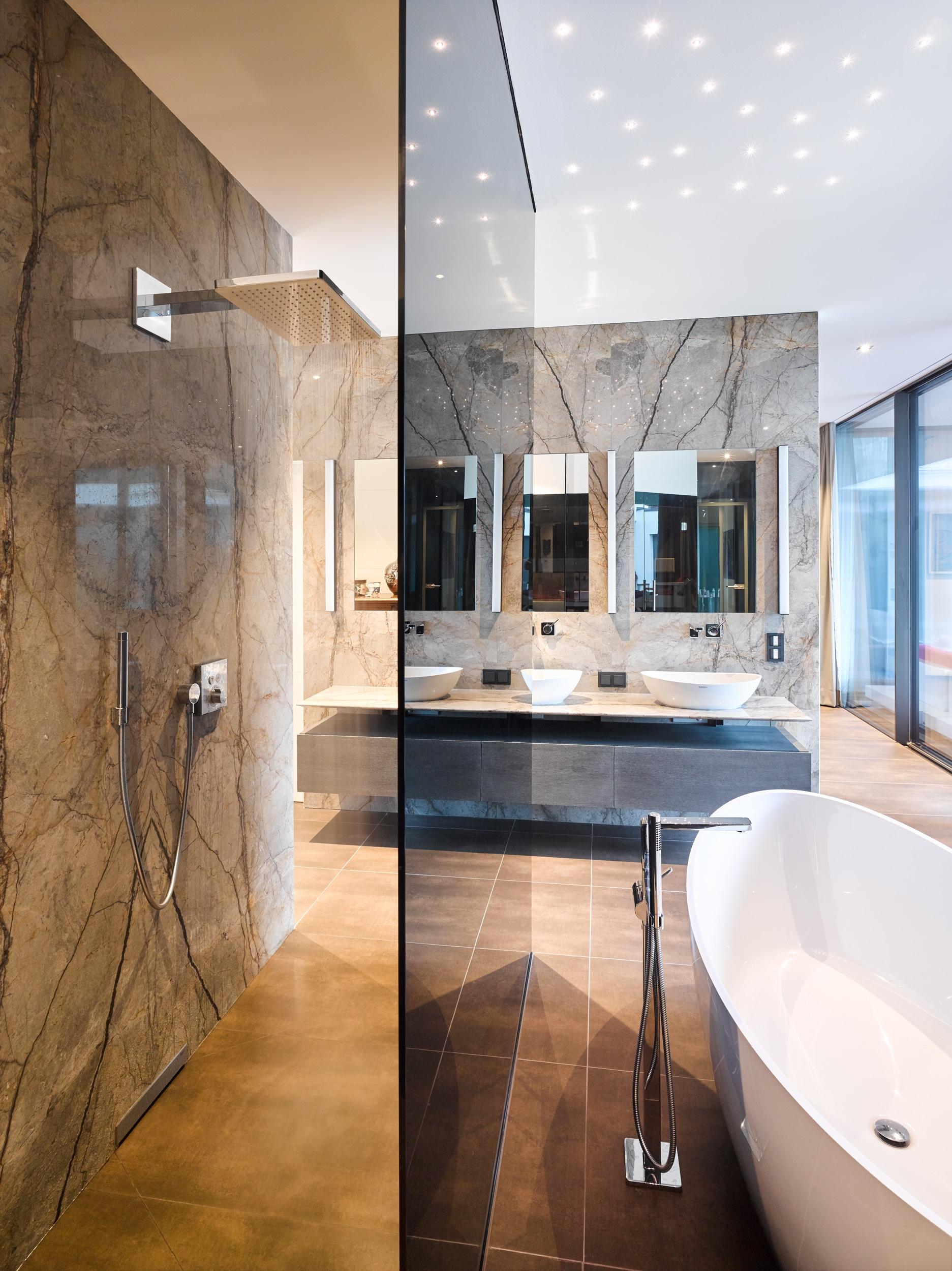 Schwarze Glaselemente wie etwa die Trennwand von der Badewanne zur elegant in den Raum integrierten Walk-in-Dusche bilden das ruhige Gegenstück zum Musterspiel des Steins. Ein in die Wand integrierter Abfluss lässt die Dusche sehr dezent wirken und bringt die große Steinwand als Trennelement perfekt zur Geltung.