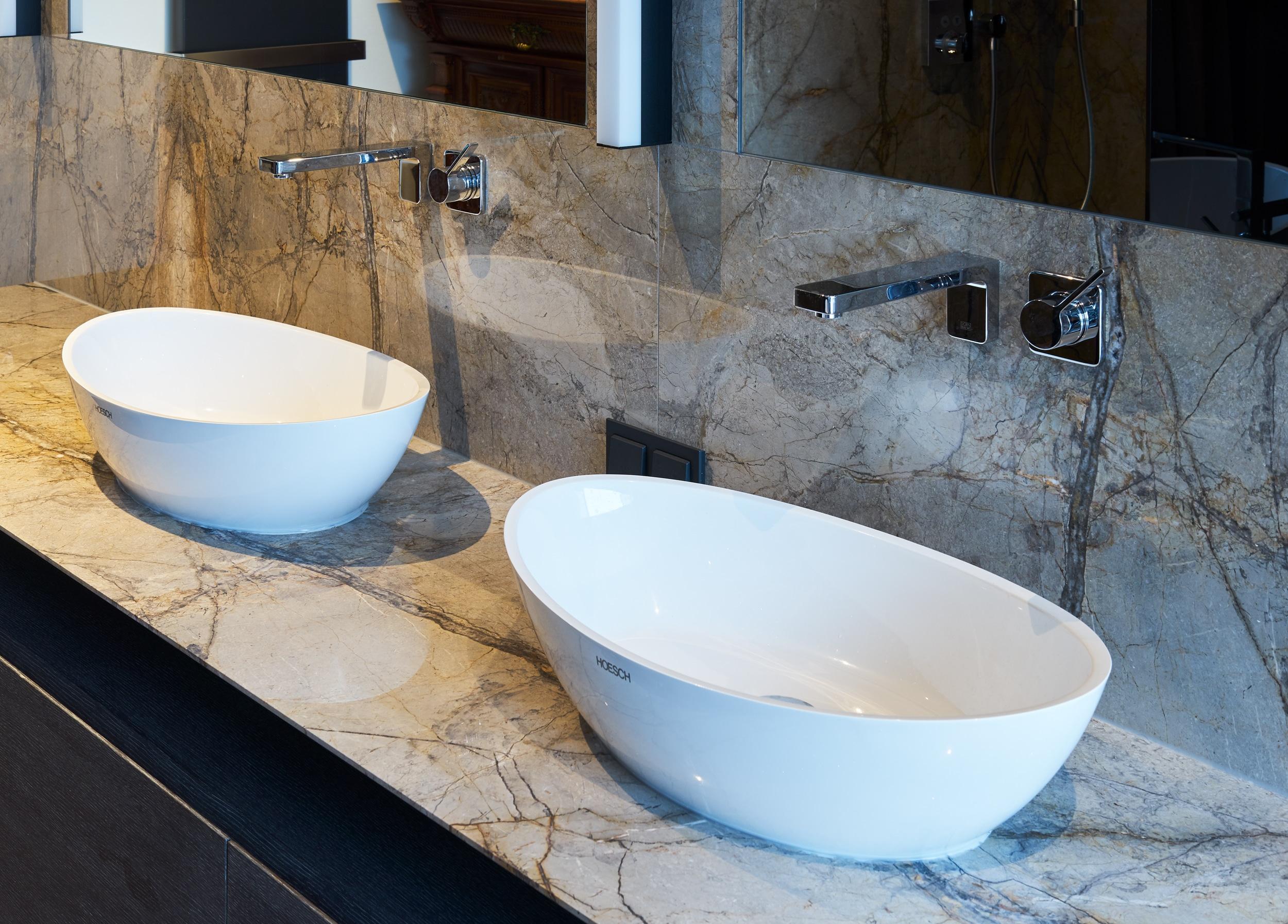 Die symmetrische Formensprache zieht sich durch das gesamte Raumkonzept, von den Leuchten über die Spiegel bis zu den beiden Waschbecken. Auf einem Natursteinelement locker platziert, wirken sie wie kleine Schiffchen auf dem Wasser.