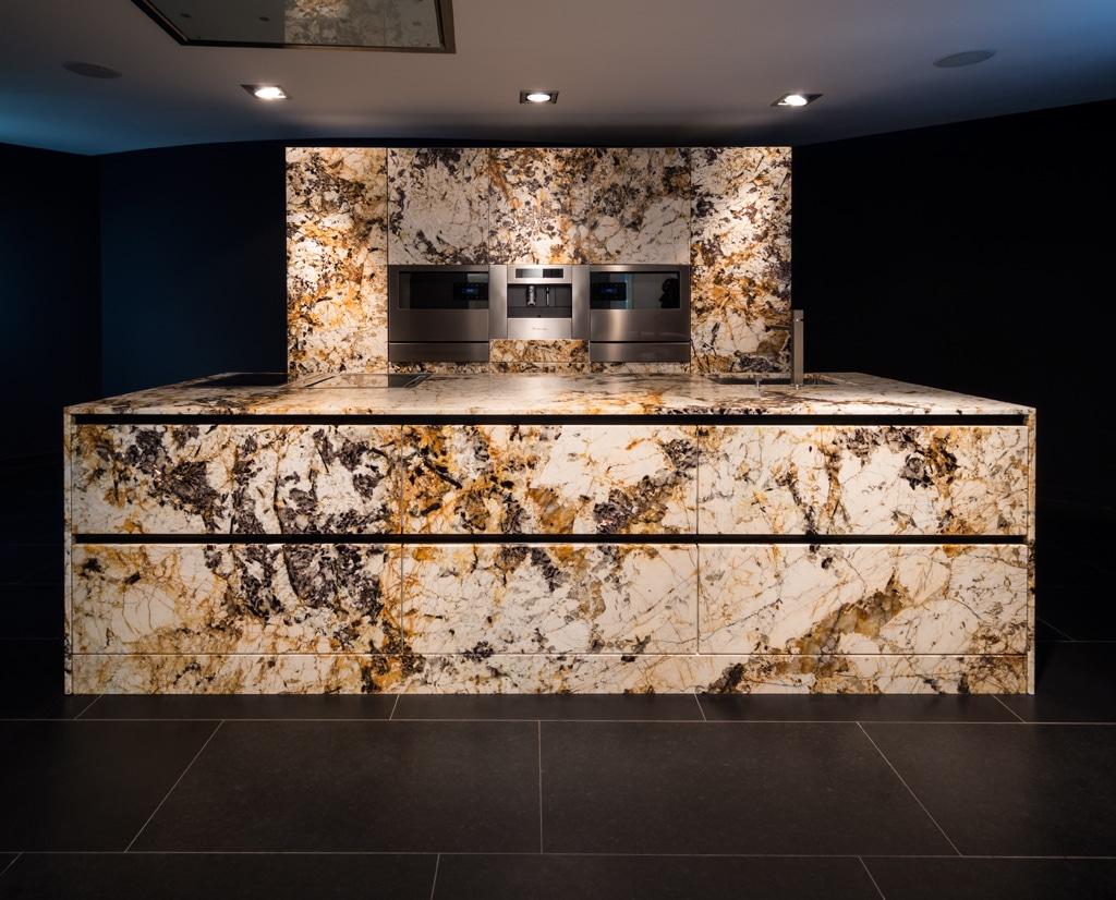 Der Küchenblock und die Rückwand der Küche Bre wurden in einem außergewöhnlichen Granit aus Brasilien ausgeführt. Rundum verkleidet, rundum funktionsfähig, rundum Mascarello Gold.