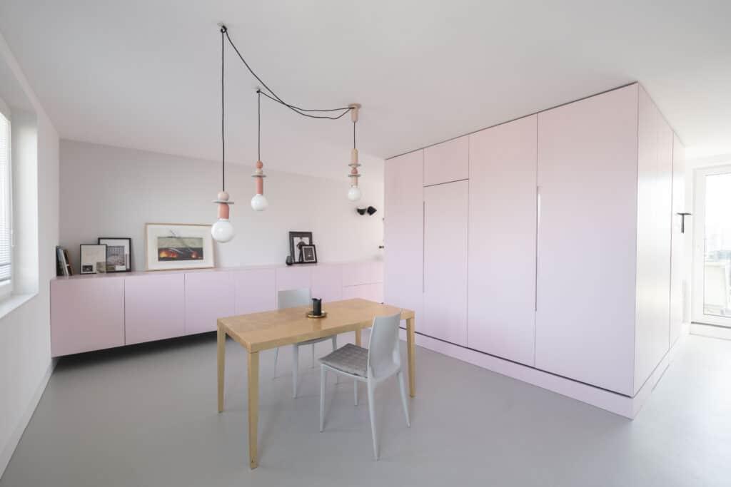 Gewohnt anders: Das Mini-Apartment in einem typischen Wiener 1970er-Jahre-Bau entzieht sich jeglicher konventionellen Typologie und kommt ohne Wände oder Türen aus. Und mittendrin in dem großen rosa Funktionsmöbel, als optischer und haptischer Kontrast, die schwarze, puristische Küchenarbeitsplatte aus dem edlen Naturstein Nero Assoluto.