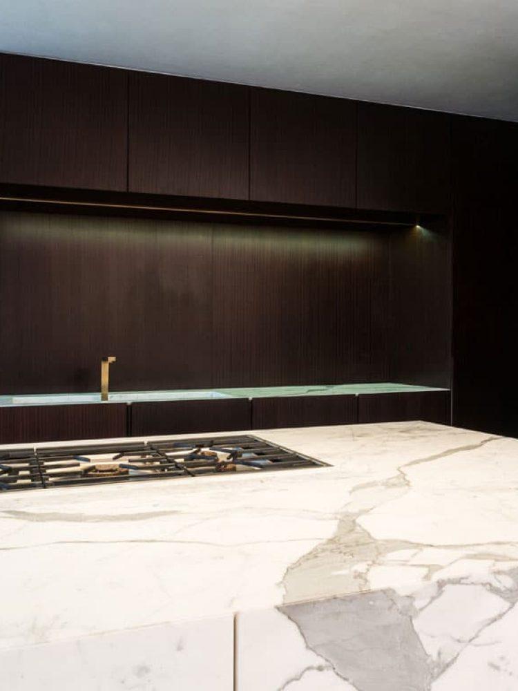 Der Küchenblock und die Arbeitsplatte in einer Wiener Stadtwohnung wurden kontrastreich in weiß-grau gemustertem Marmor und dunklem Holz ausgeführt.